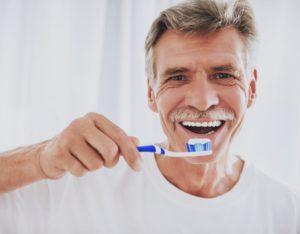 older man brushing his dental implants